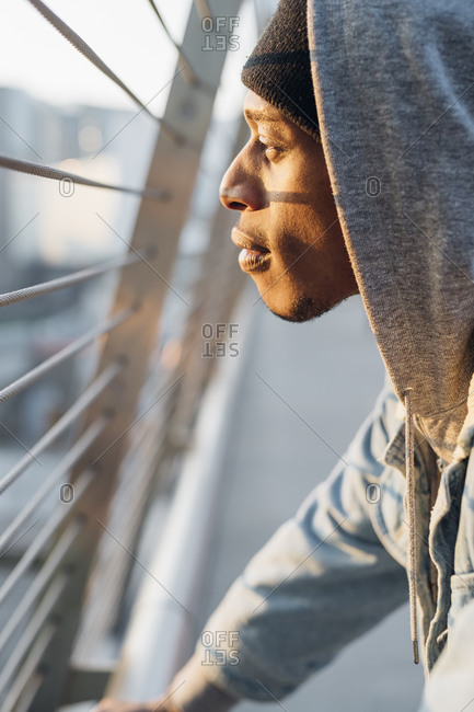 Profile of young man looking through metal bars at sunset