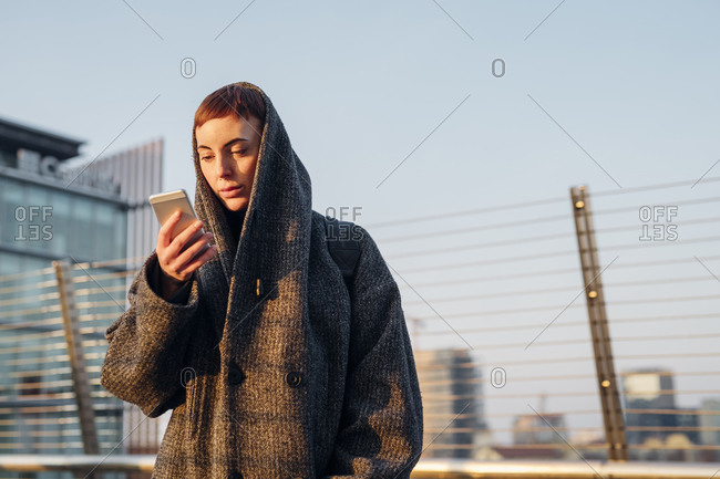 Redheaded young woman using smartphone on a bridge in the city