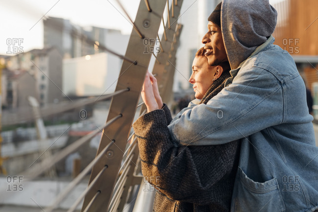 Affectionate young couple on a footbridge at sunset