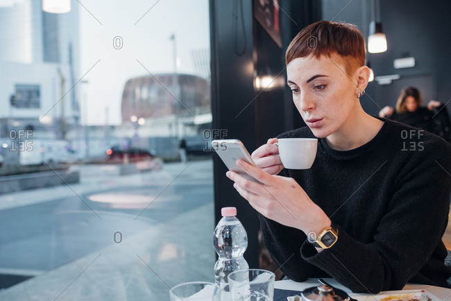 Redheaded young woman using smartphone in a cafe