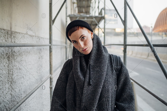 Portrait of young woman under a scaffolding in the city