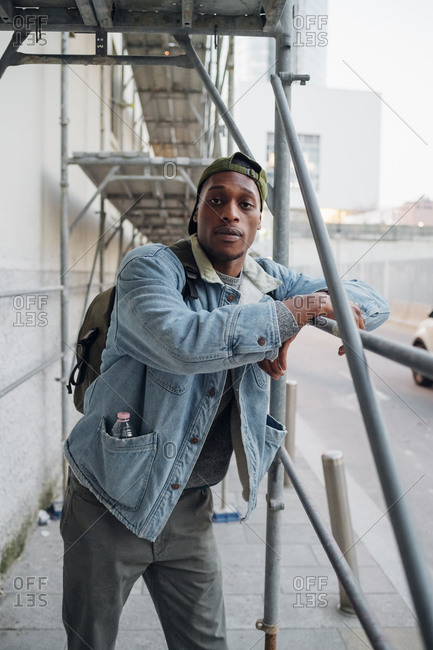Portrait of young man standing at a scaffolding in the city