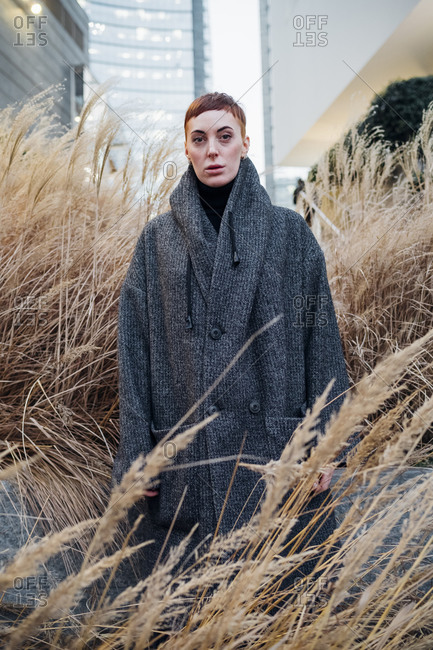 Portrait of young woman among grasses in the city