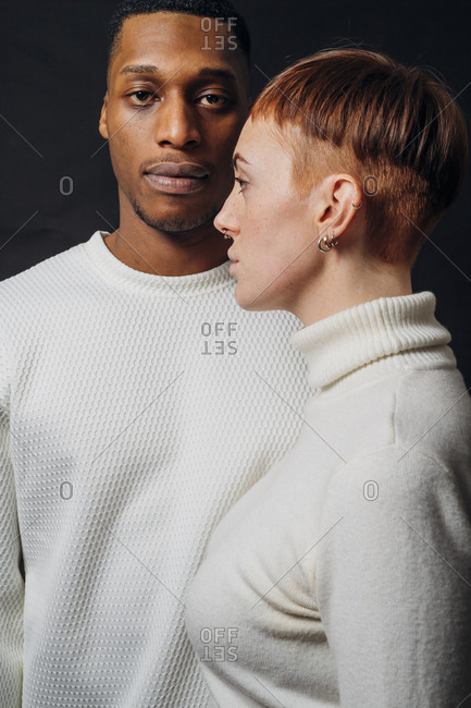 Studio portrait of mixed race couple wearing white sweaters