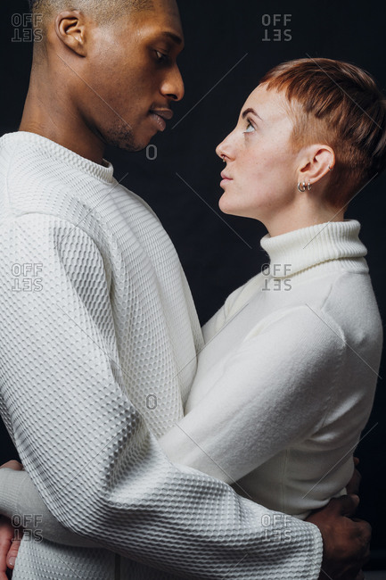 Studio portrait of affectionate mixed race couple embracing