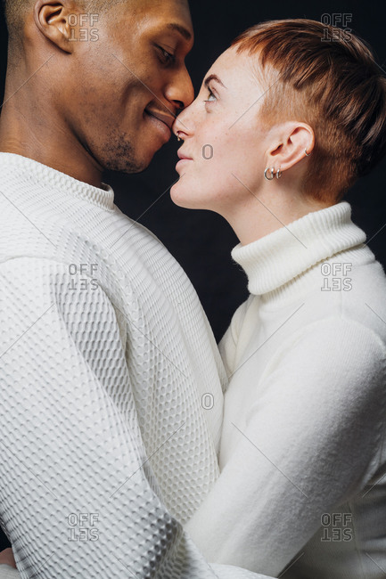 Studio portrait of affectionate mixed race couple face to face