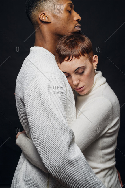 Studio portrait of affectionate mixed race couple hugging