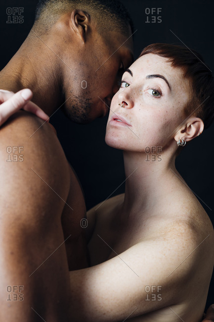 Studio portrait of affectionate nude mixed race couple hugging