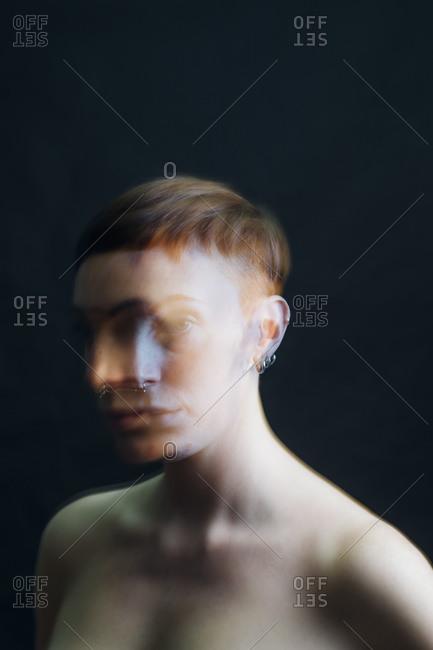 Double exposure portrait of nude young woman in studio