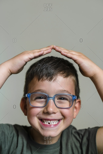 Portrait of little boy with tooth gap wearing blue glasses