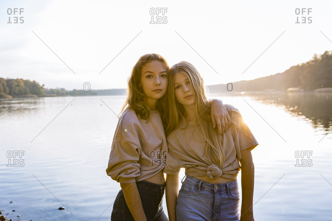 Portrait of friends standing with arm around against lake during sunset
