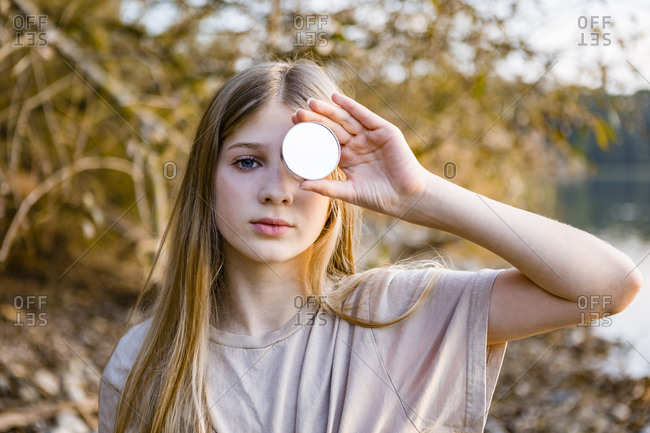 Portrait of girl holding mirror in front of eye during sunset