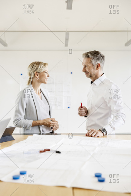 Smiling businesswoman and businessman leading in conference room