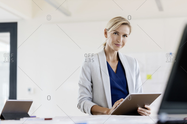 Blond businesswoman using tablet in conference room