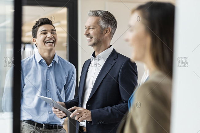 Smiling mature businessman and employees in office
