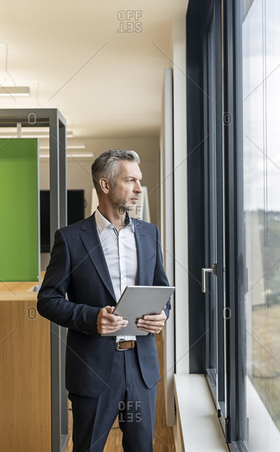 Mature businessman with tablet in office looking out of window