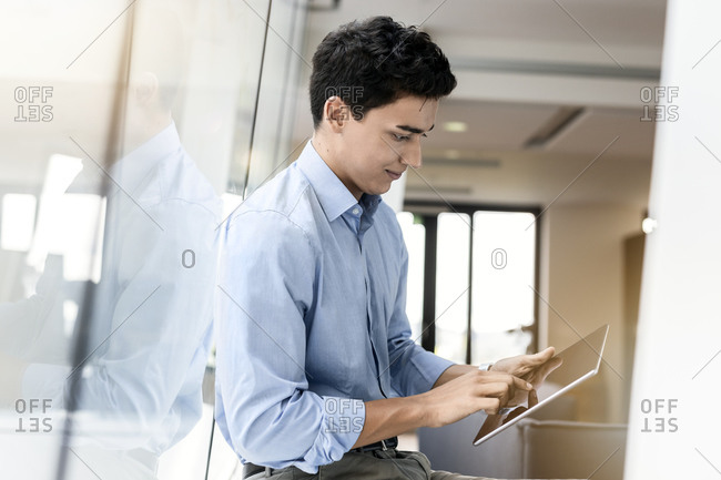 Young businessman using tablet at the window in office