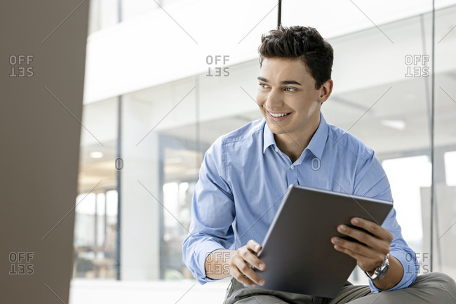 Portrait of smiling young businessman with tablet at the window in office