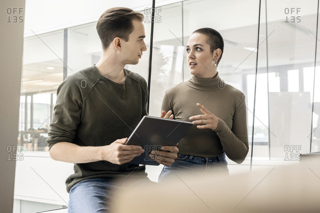 Young woman and man with tablet talking at the window in office