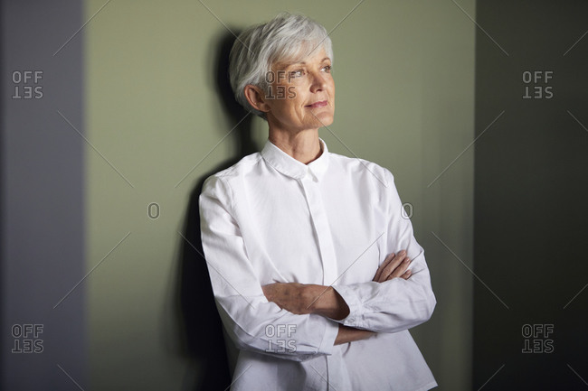 Portrait of senior businesswoman leaning against wall looking at distance