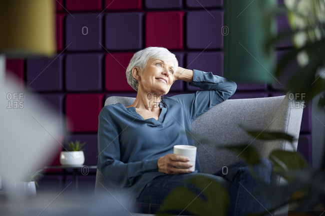 Portrait of smiling senior businesswoman sitting on lounge chair looking at distance