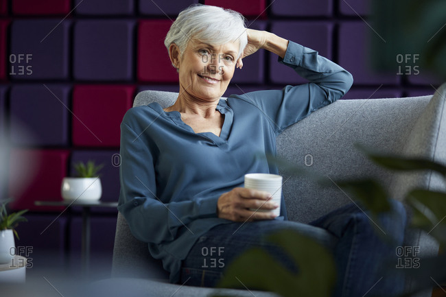 Portrait of smiling senior businesswoman sitting on lounge chair with coffee mug