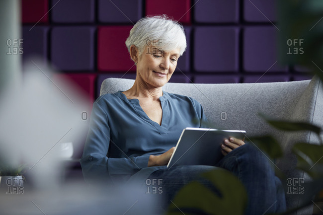 Portrait of senior businesswoman sitting on lounge chair using digital tablet