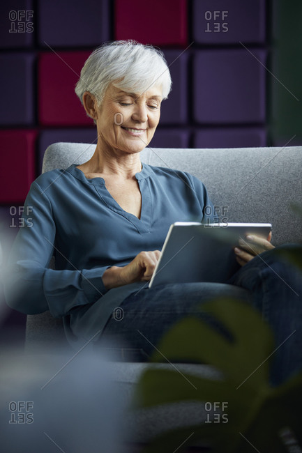 Portrait of smiling senior businesswoman sitting on lounge chair using digital tablet