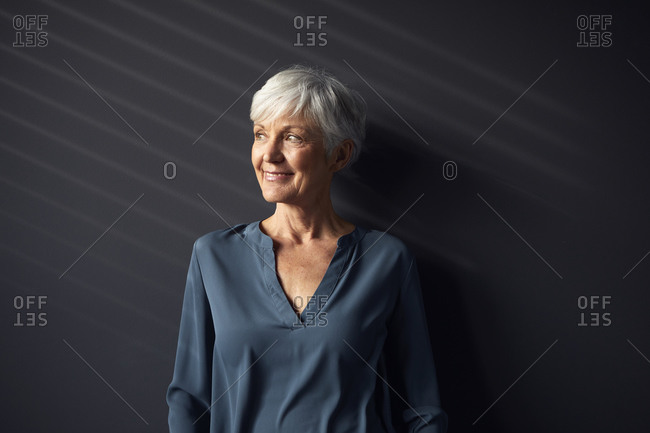 Portrait of smiling senior woman against grey wall looking at distance