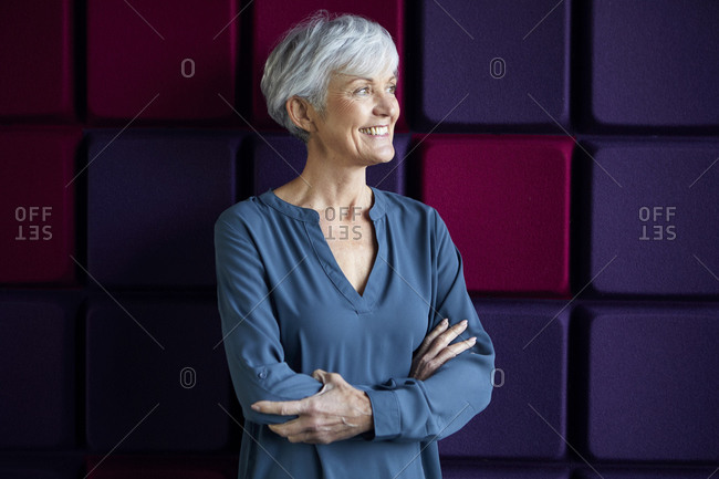 Portrait of happy senior woman with arms crossed looking at distance