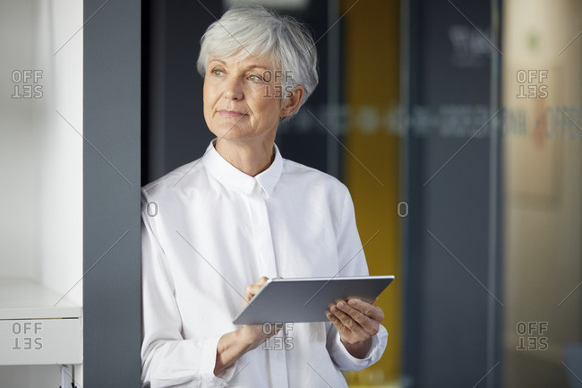 Portrait of senior businesswoman with digital tablet in office