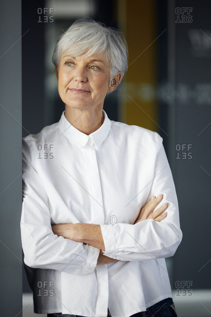 Portrait of content senior businesswoman looking at distance