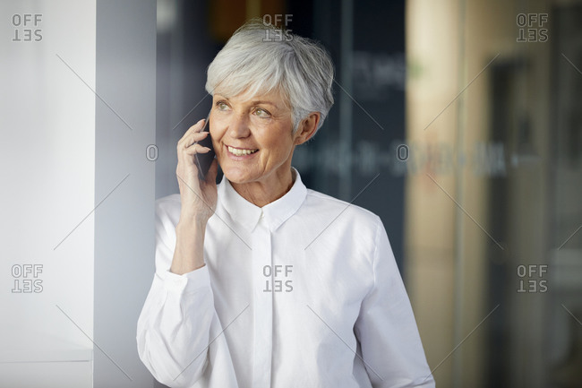 Portrait of smiling senior businesswoman on the phone looking at distance