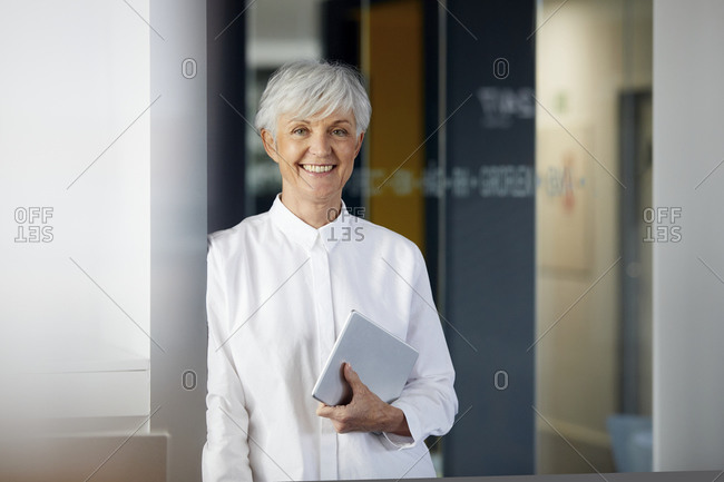 Portrait of smiling senior businesswoman with digital tablet in an office