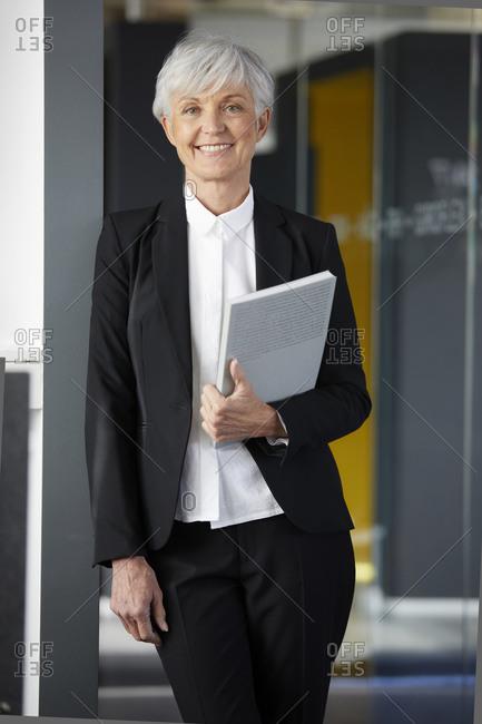 Portrait of content senior businesswoman wearing black pantsuit