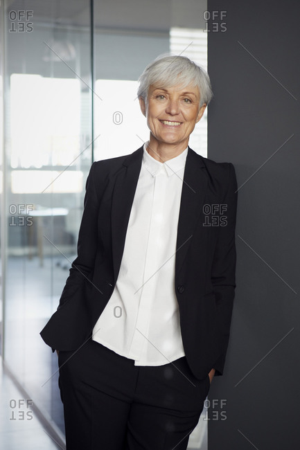 Portrait of smiling senior businesswoman wearing black pantsuit