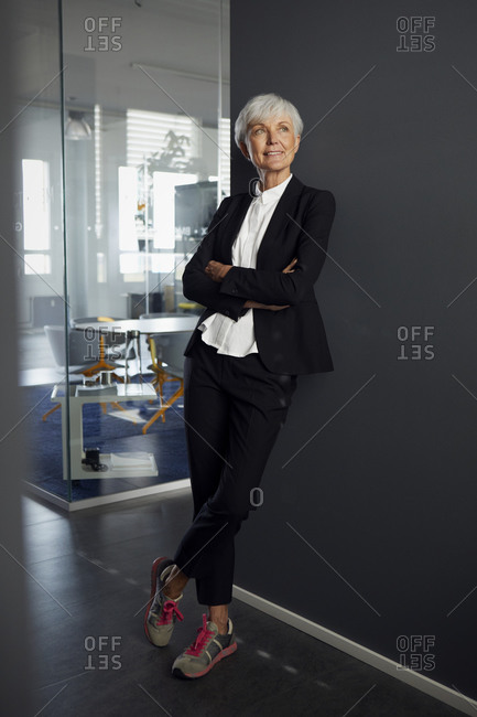 Portrait of fashionable senior businesswoman wearing pantsuit and sneakers in office