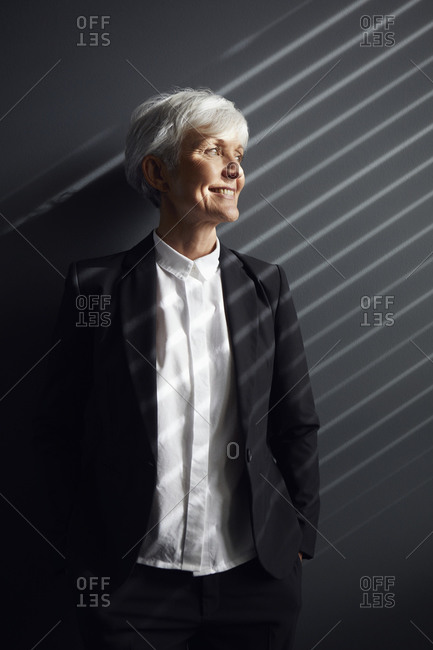 Portrait of fashionable senior businesswoman in front of grey wall looking at distance