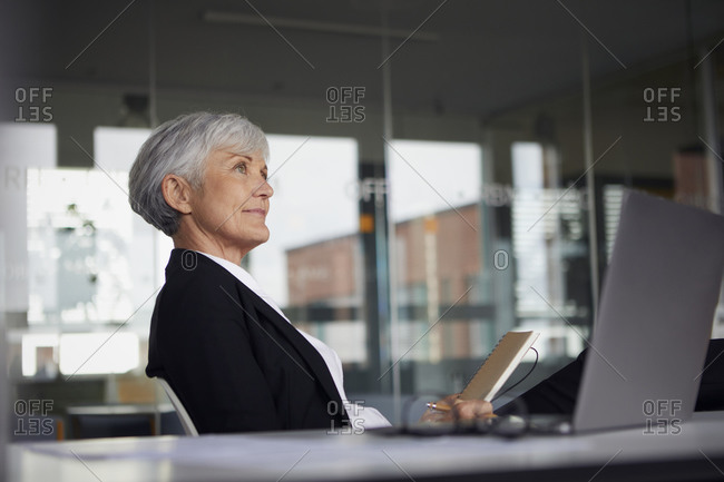 Senior businesswoman sitting at desk in office looking at distance