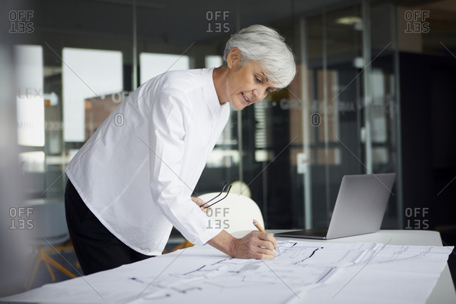 Portrait of architect working on construction plan in office