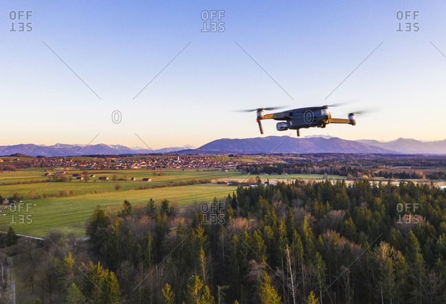 Germany- Bavaria- Konigsdorf- Drone flying over rural grove at dusk