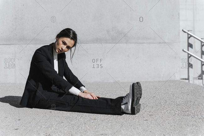 Young woman wearing black suit sitting on floor in front of concrete wall