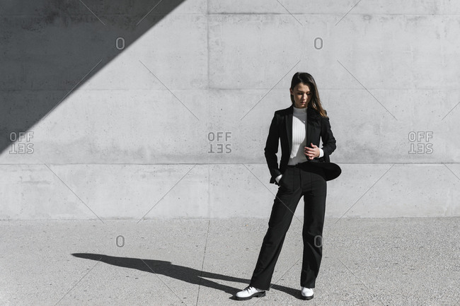 Young woman wearing black suit standing in front of concrete wall