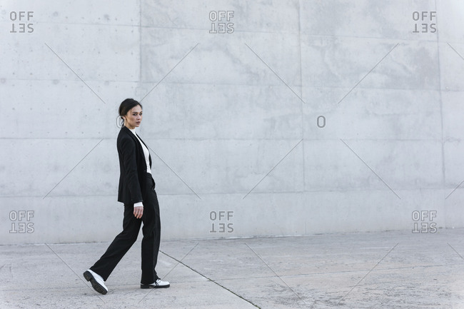 Young woman wearing black suit walking in front of concrete wall