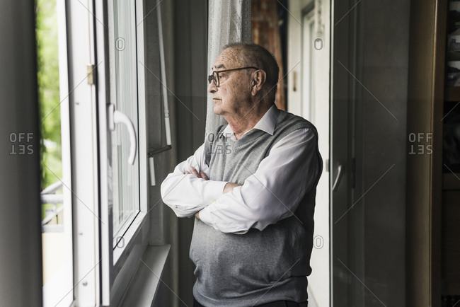 Pensive senior man looking out of window