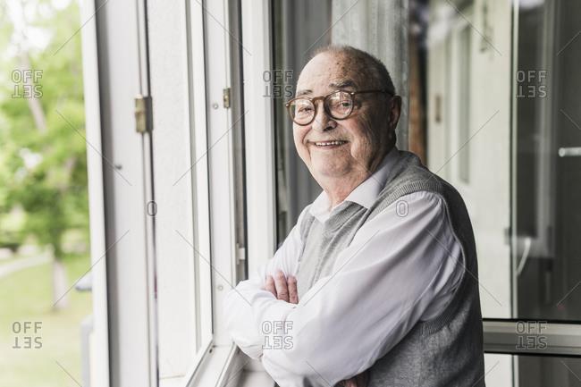 Portrait of smiling senior man standing at open window