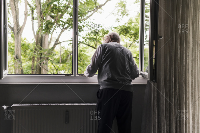 Back view of senior man looking out of window