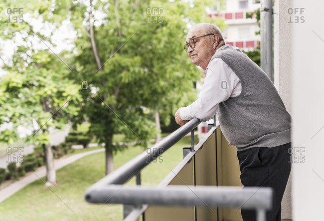 Senior man standing on balcony looking at distance