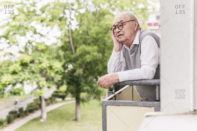 Portrait of senior man standing on balcony looking at distance
