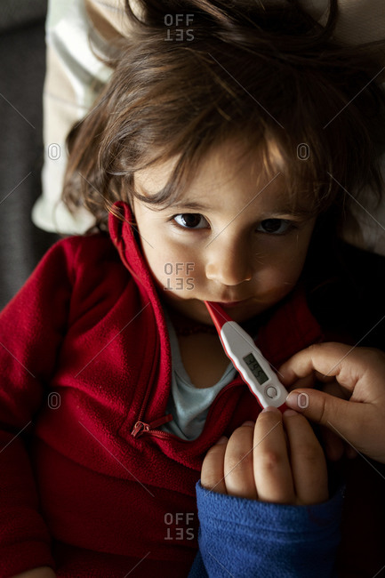 Portrait of sick girl lying on couch with digital thermometer- mother's hands